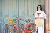 Beautiful women Vietnam with white Ao Dai dress and red bicycle in old city selective and soft focus of face color vintage style poster