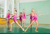 Group of preteen girls, professional gymnasts present their performance with hula hoops in sports hall poster
