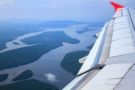 Airplane flying above mangroves forest view from airplane window