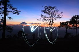drawing light two hearts by flashlight in the air in the forest before sunrise