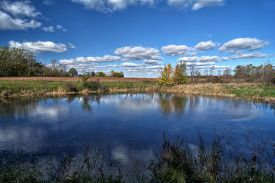 A beautiful autumn day at a small tree lined country pond in Ohio with a pretty blue sky with white puffy clouds reflecting in the water.