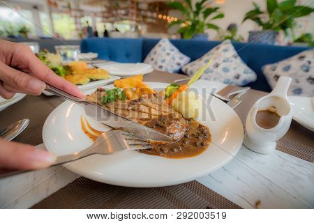 Cutting The Steak By Knife In White Dish While Take A Dinner, To Enjoy With The Main Course