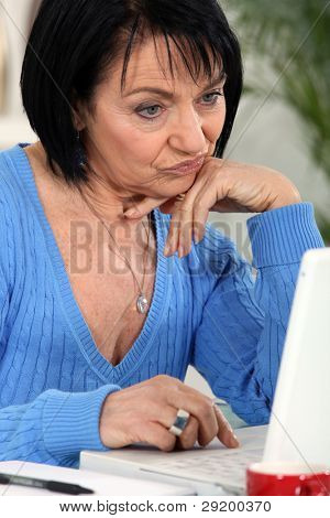 Annoyed woman looking at her laptop