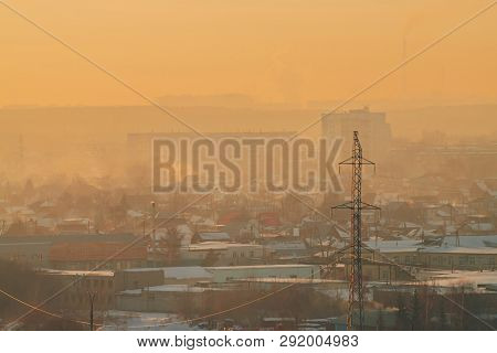 Power Lines In City On Dawn. Silhouettes Of Urban Buildings Among Smog On Sunrise. Cables Of High Vo
