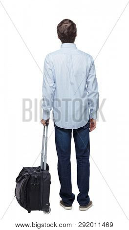 Back view of business man with suitcase Standing young guy. Rear view people collection.  backside view of person. Isolated over white background. A young traveler stands leaning on a suitcase.