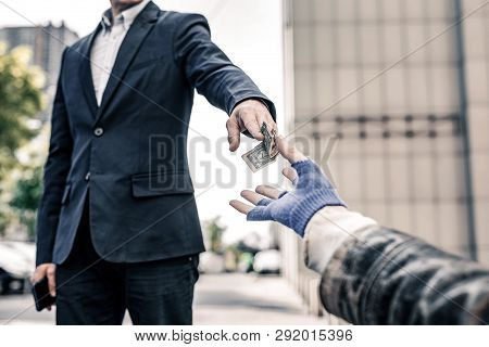 Generous Good-looking Man In Dark Costume Sharing His Money With Homeless