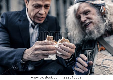 Sincere Kind Man In Office Costume Sharing Sandwich With Homeless Man