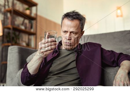 Serious Depressed Man Observing Alcohol In Glass And Deeply Thinking