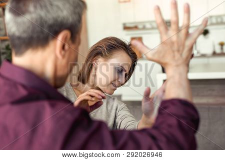 Grey-haired Furious Adult Man Beating His Crippled Dark-haired Wife