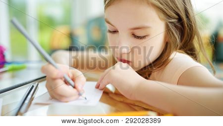 Cute Little Girl Drawing With Colorful Pencils At A Daycare. Creative Kid Painting At School. Girl D