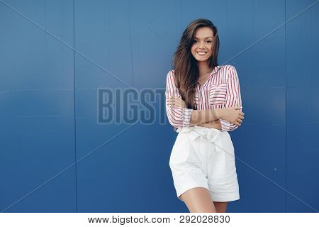 Fashion Portrait Of A Sensual Woman. External Photo Of An Attractive Brunette Model In A White Skirt