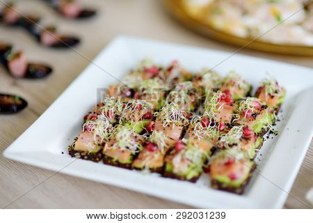 Delicious Smoked Salmon And Avocado Mini Snacks Served On A Party Or Wedding Reception. Plates With