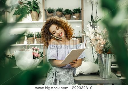 Young beautiful florist calling her client and identifying some details poster