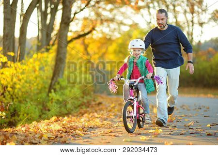 Happy Father Teaching His Little Daughter To Ride A Bicycle. Child Learning To Ride A Bike On Sunny