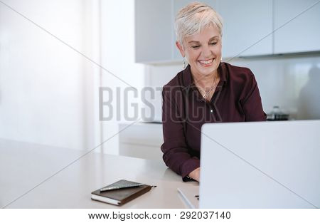 Portrait Of A Beautiful Mature Woman Smiling, Typing On Her Laptop, In The Kitchen. Shot With Copysp