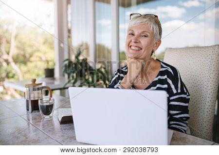 Beautiful Senior Woman Using Laptop At Home. Mature Smiling Woman Looking At Camera While Working Wi