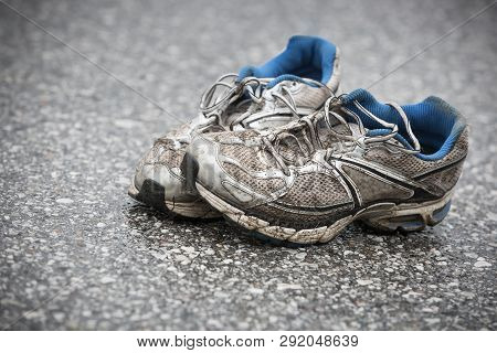 Worn, Dirty, Smelly And Old Running Shoes On A Tarmac Road. Road Running, Endurance, Marathon Afterm