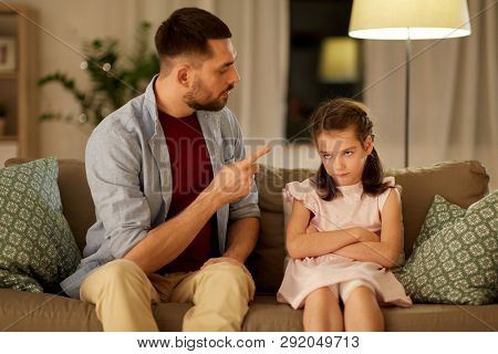parenting, family and people concept - upset or feeling guilty girl and father at home