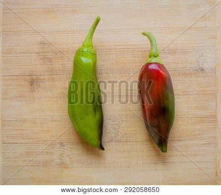 Top View Of Freshly Harvested Organic Green And Red Peppers On A Wooden Cutting Board.
