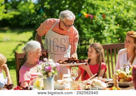 leisure, holidays and people concept - happy family having festive dinner or barbecue party at summer garden