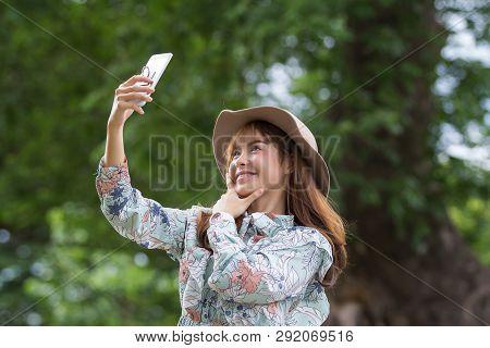 Beautiful Asian Woman Relaxing By Selfie In Park