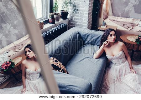 Wedding. Bride In Beautiful Dress Sitting Near Sofa Indoors In White Interior Like At Home. Trendy W