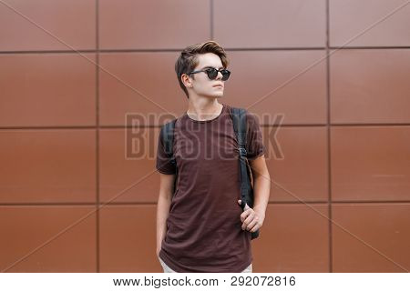 American Stylish Hipster Young Man In A Stylish T-shirt In Black Sunglasses With A Fashionable Hairs