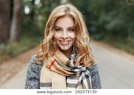 Portrait Of A Joyful Cute Young Woman With A Smile With Blue Eyes In An Elegant Coat With A Checkere