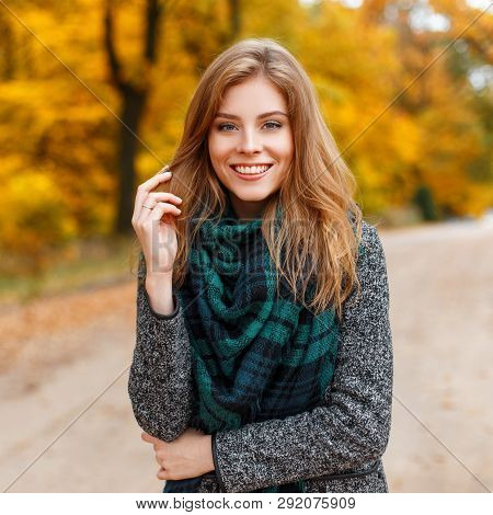 Positive Attractive Young Woman In A Warm Gray Fashionable Modern Outerwear With A Green Scarf In Th