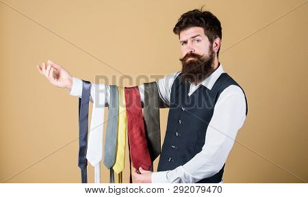 This Tie Is A Must Have. Brutal Hipster Holding Colorful Tie Collection. Bearded Man Choosing Neck T