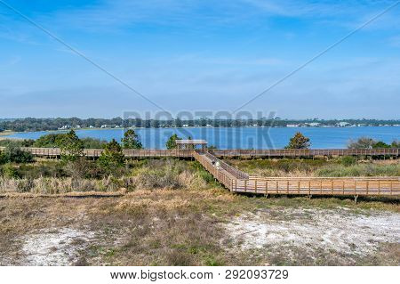 A Very Long Boardwalk Surrounded By Shrubs In Gulf Shores, Alabama