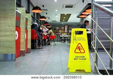 Minsk, Belarus, March 13, 2019: Sign Showing Warning Of Caution Wet Floor In A Kfc Restaurant.