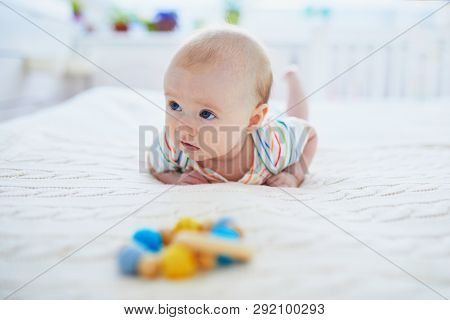 Adorable Baby Girl Lying On Bed On Her Tummy. Happy Healthy Little Child Practice Crawling. Infant K