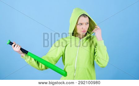 Woman Play Baseball Game Or Going To Beat Someone. Girl Hooded Jacket Hold Baseball Bat Blue Backgro