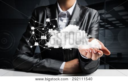 Businessman In Suit Keeping Cloud With Network Connections In Hand With Dark Office View On Backgrou