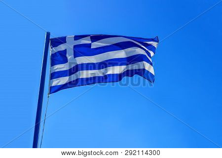 Flag Of Greece On A Beautiful Blue Sky. Diplomacy Concept, International Relations.