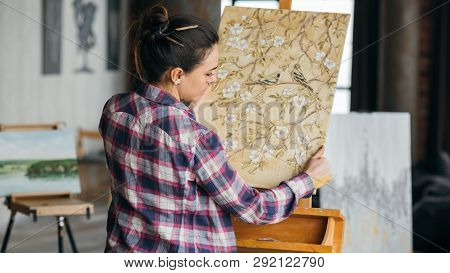 Finished Artwork. Flower Blossom And Birds Canvas. Art Studio Workspace. Woman Artist Looking At Pai