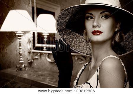 Beautiful woman in hat in luxury interior.