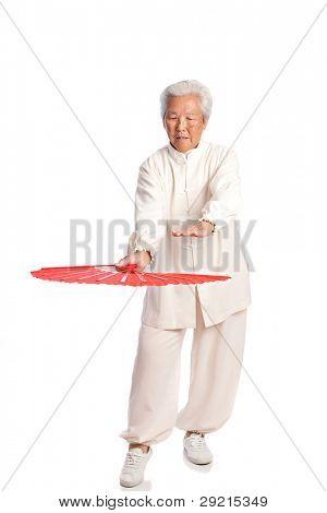 Chinese Elderly Woman Performing Tai Chi with Red Fan Isolated on White Background