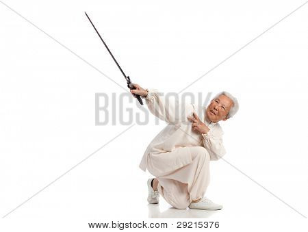 Chinese Elderly Woman Performing Tai Chi with Sword Isolated on White Background