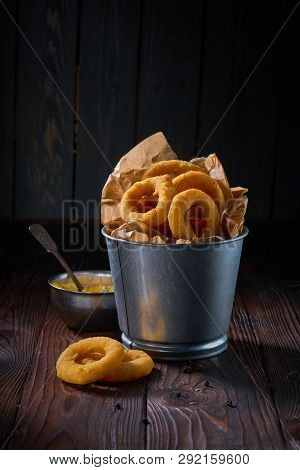 Fried Onion Rings With Sauce Served In Metal Backet On Wooden Table
