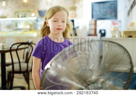 Cute Little Girl Standing In Front Of A Fan On Hot Summer Day. Child Enjoying Cool Wind In Summer Se