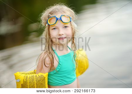 Cute Young Girl Wearing Swimsuit Playing By A River On Hot Summer Day. Adorable Child Having Fun Out