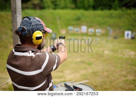 Man Shooting On An Outdoor Shooting Range. Male Aiming Gun At Firing Range.