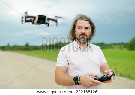 Man Watching And Navigating A Drone. Bearded Man Operating The Drone By Remote Control. Drone Hoveri