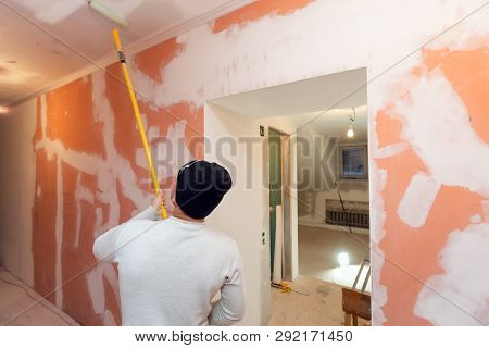 Worker Is Painting The Ceiling By Paint Roller In Corridor  An Apartment Is Inder Construction, Remo