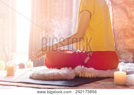 A Girl Surrounded By Candles At Home At The Window Meditates In The Lotus Position Making Fingers Mu