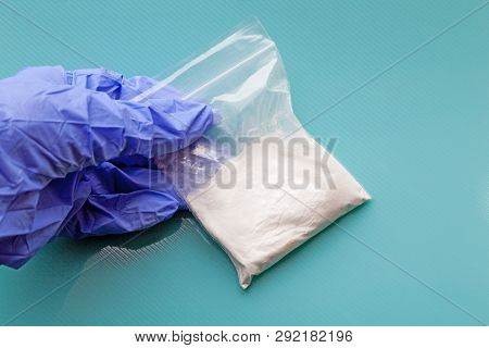 Seized Drugs Concept - Gloved Hand Holding A Bag Containing  A White Powdered Substance