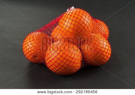 Oranges In Bag Mesh On Dark Background