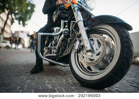 Biker poses on motorcycle, front view from ground